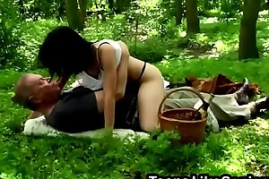 A naughty brunette teen sucks a dick of a horny older man in a forest